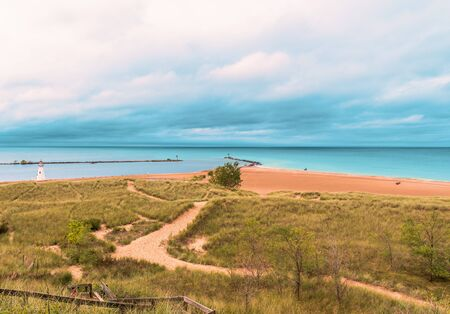 Sandy dunes and grass in the harbor at New Buffalo, Michigan on the lake.  Dramatic sky front coming in before it rains on a hilly sandy path leading to the beach. Reklamní fotografie