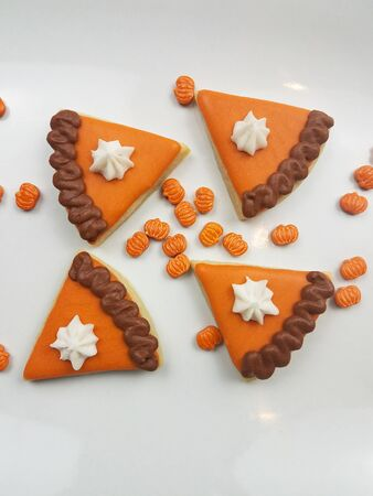 Closeup of fall mini pumpkin pie sugar cookies on a platter with pumpkin sprinkles to celebrate the holiday Stock Photo