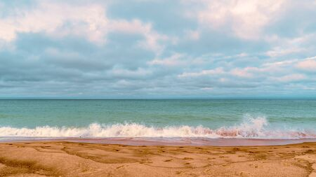 Cloudy, moody shot of lake michigan beachfront and crashing waves on the sand before it rains