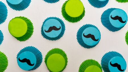 Blue and green mustache cupcake papers themed for fathers day, a baby shower, or kids birthday party.