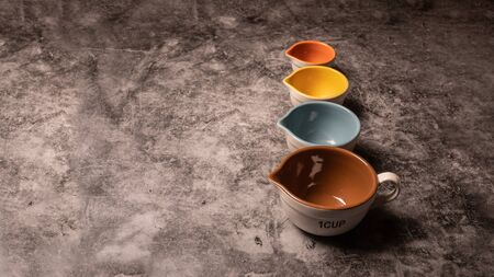 Many measuring cups sitting on a slate countertop