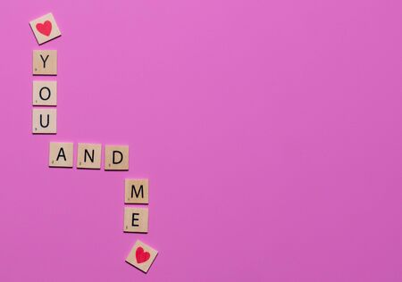 Colorful You and Me game tiles with hearts on a pink background to celebrate love