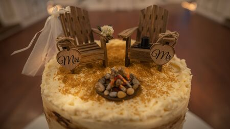 Side view of a rustic style wedding cake themed around camping. Close up of adirondack chairs cake topper on a bark-style tiered cake saying Mr. and Mrs.