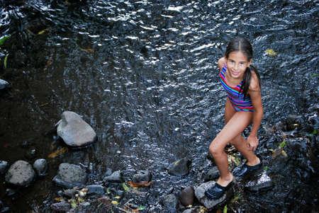 Edad de Piedra: Chica caminando en la senda de piedra a trav�s de un r�o Foto de archivo