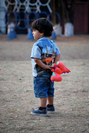 Little boy holding a stuffed animal behind his back photo