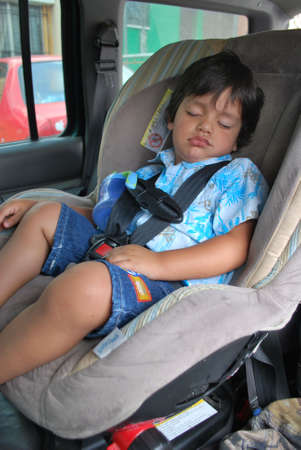 Little boy sleeping in his big comfy car seat photo
