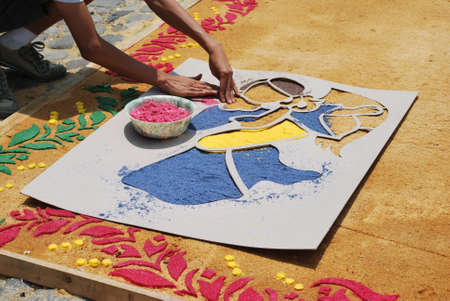 Someone creating a carpet for a procession using colored sawdust in Antigua, Guatemala