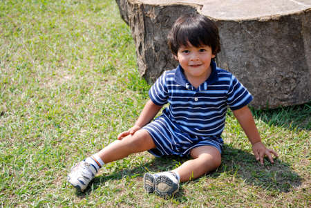 Cute little Hispanic boy sitting outside on the grass