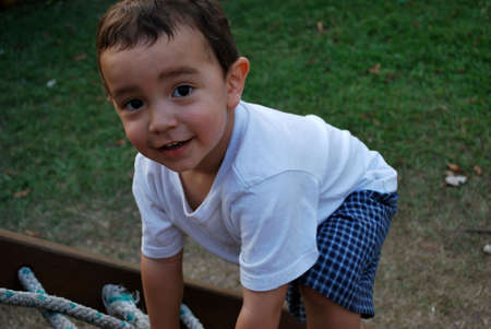 Cute little boy climbing a rope ladder on the playground photo