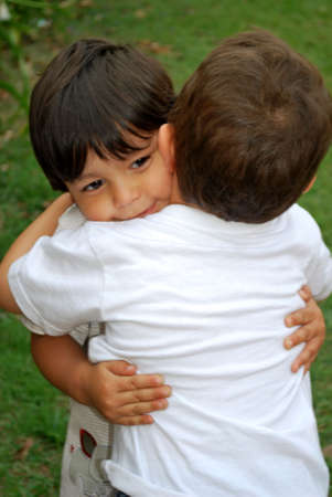 Two cute little boys hugging each other photo