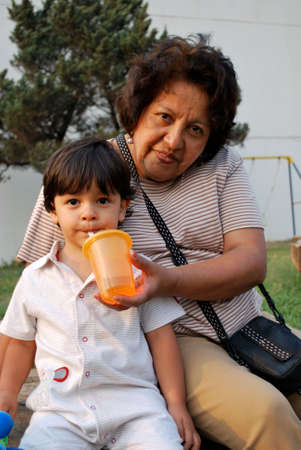 three generations of women: Grandmother giving water to her grandson