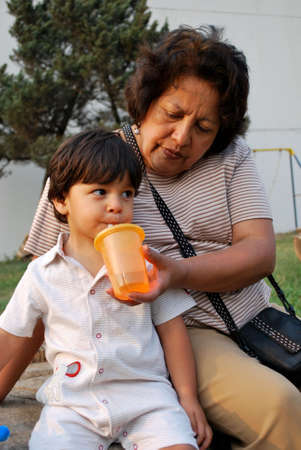 Grandmother giving water to her grandson