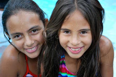 Beautiful Hispanic sisters by the pool