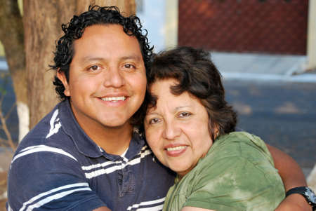 three generations of women: Middle aged Hispanic mother and grown son Stock Photo