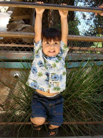 Adorable kleinen Jungen an einem Stock hängt