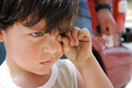 Little boy rubbing his eyes.  A man's fist is behind him. Stockfoto