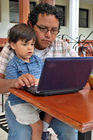 Hispanic father and son use the computer together