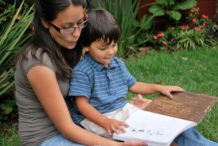 babysitter: Young Hispanic mother reads with her son
