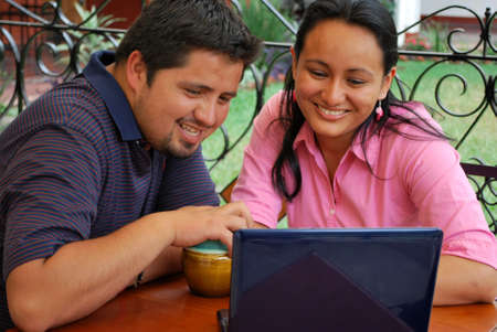 A young happy Hispanic couple on the computer togehter