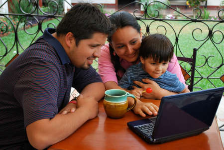 Young couple on computer with their toddler photo