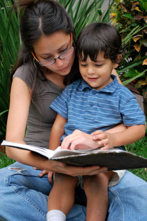 Young Hispanic mother and son reading together photo