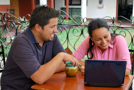 Young Hispanic couple laughing at an internet cafe photo