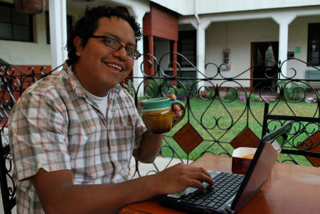 Hispanic man sipping coffee and working on his laptop computer photo