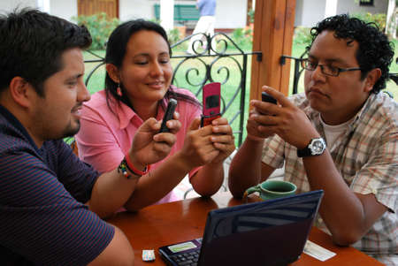 Young Hispanic students sending messages on their cellphones photo