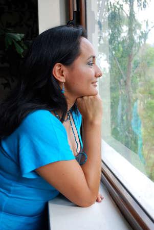 Beautiful Hispanic woman looking out the window Фото со стока