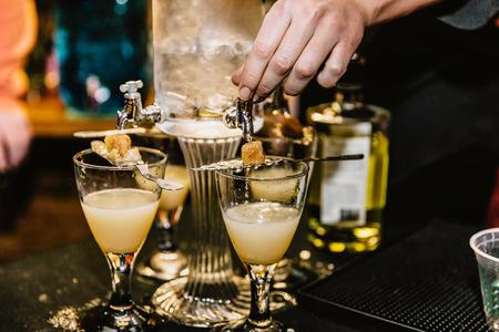 Préparation à la main de cocktails à base d'absinthe lors d'un événement
