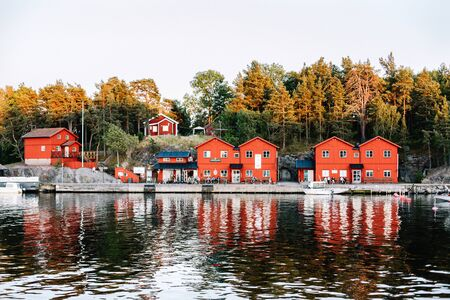 View of traditional Swedish architecture while on a sunset cruise. Red buildings can be seen scattered along the archipelago in Stockholm, Sweden