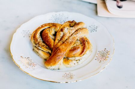 Delicious traditional Swedish pastry, Kanelbulle on a vintage porcelain plate in Stockholm, Sweden Stok Fotoğraf