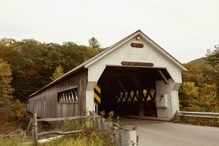West Dummerston covered bridge surrounded by Fall foliage in the New England town of Dummerston, Vermont