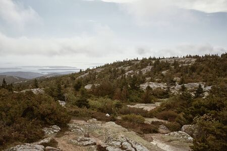 Hiking along granite bedrock on the summit of Cadillac Mountain in Acadia National Park on Mount Desert Island, Maine.
