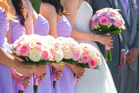 Eine Braut und ihre Brautjungfern halten Blumensträuße auf einer Hochzeit. Standard-Bild - 56528668