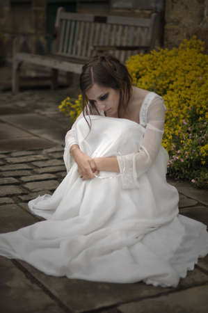 Goth bride, sitting on stone