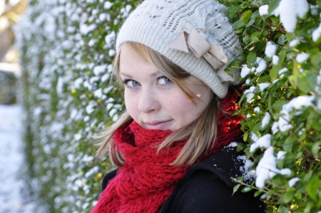 innocent blonde in a snowy hedgerow