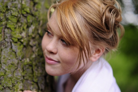 bridesmaid peeking round a mossy tree