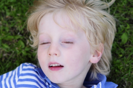 sleeping kid: pale blonde boy relaxing on grass Stock Photo