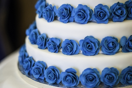 Three tier white and blue rose wedding cake Stock Photo
