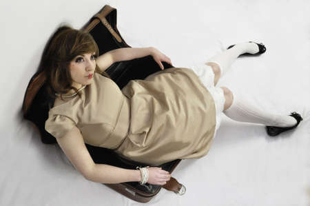 dolly: human vintage doll in leather suitcase from above Stock Photo