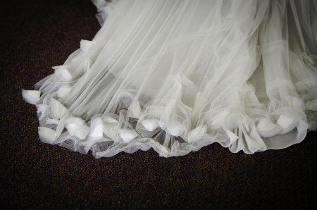 textured sheer wedding dress train with fabric flower buds closeup
