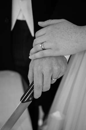 bride and groom hands holding knife to cut cake