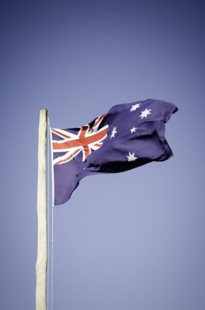raised Australian Flag blowing in the wind Stock Photo