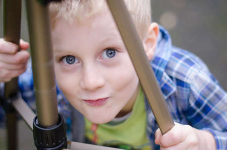 blonde blue-eyed boy posing behind tripod with quirky expression Stock Photo