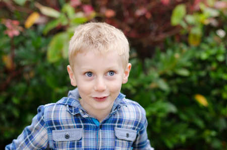 excited wide-eyed blonde boy kid with blue eyes in blue checked shirt