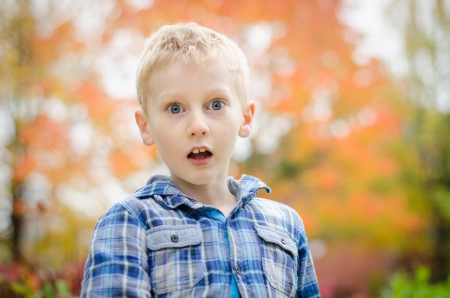 startled young boy with autum fall leaves in background Stock Photo