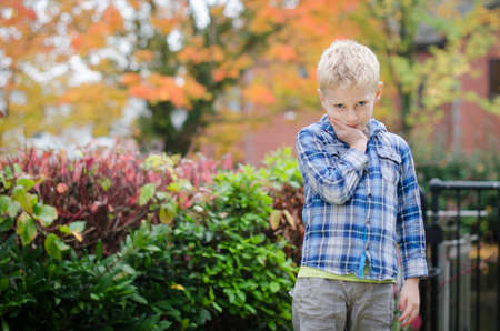 young boy thinking or scheming or deliberating with autumn fall leaves