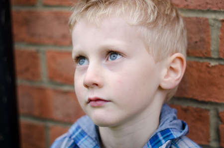 innocent young boy in alleyway, looking thoughtful, colour