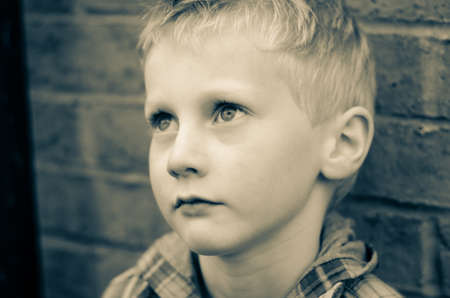 innocent young boy in alleyway, looking thoughtful monochrome Stock Photo